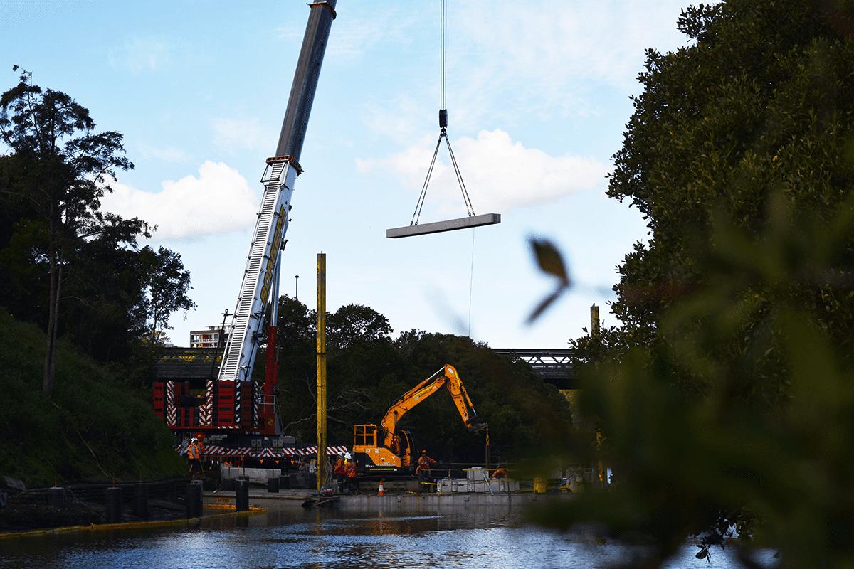 A crane lowering a concrete beam onto the Paramatta boardwalk