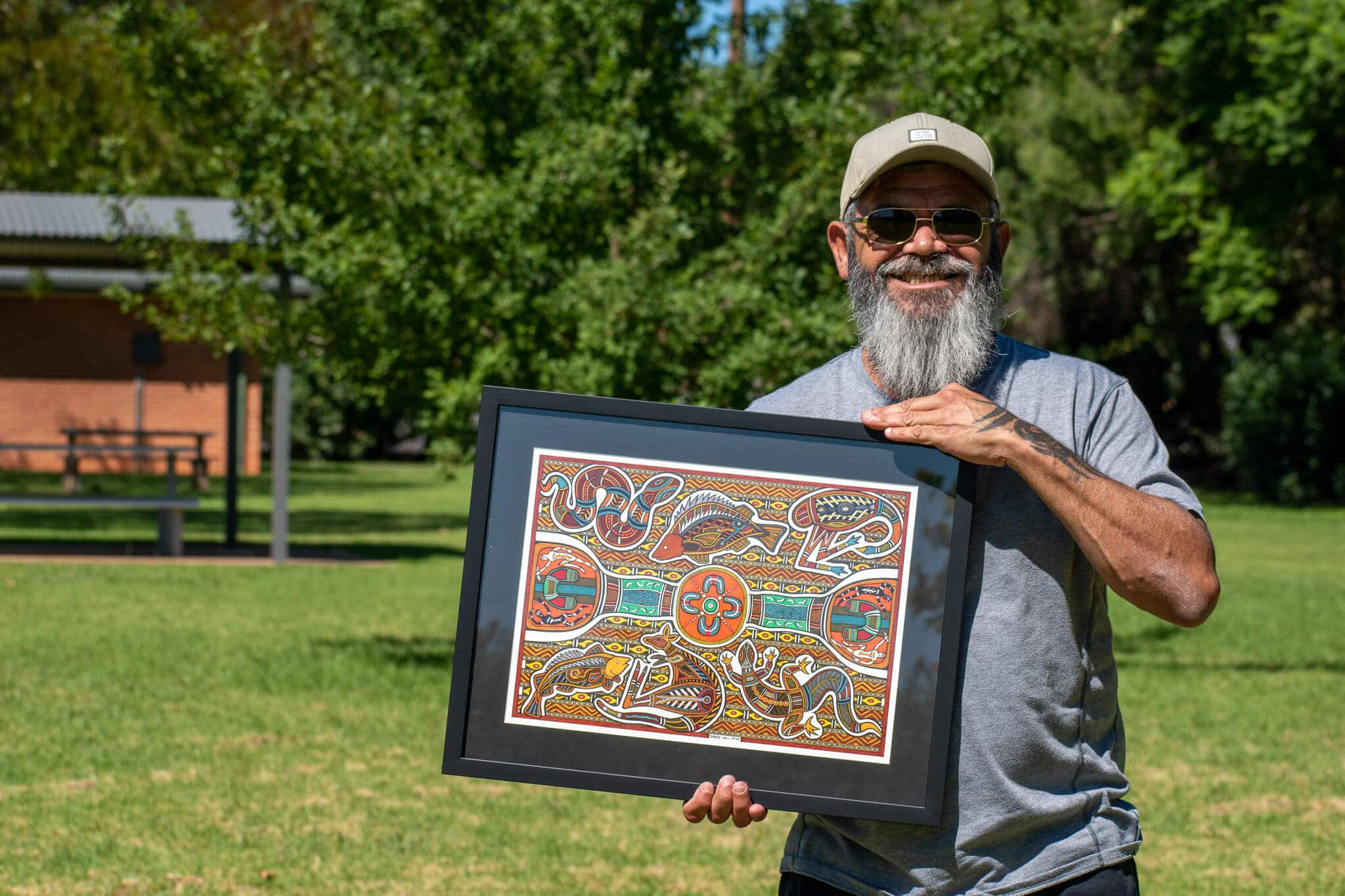 Wiradjuri Artist holding his finished artwork in a park