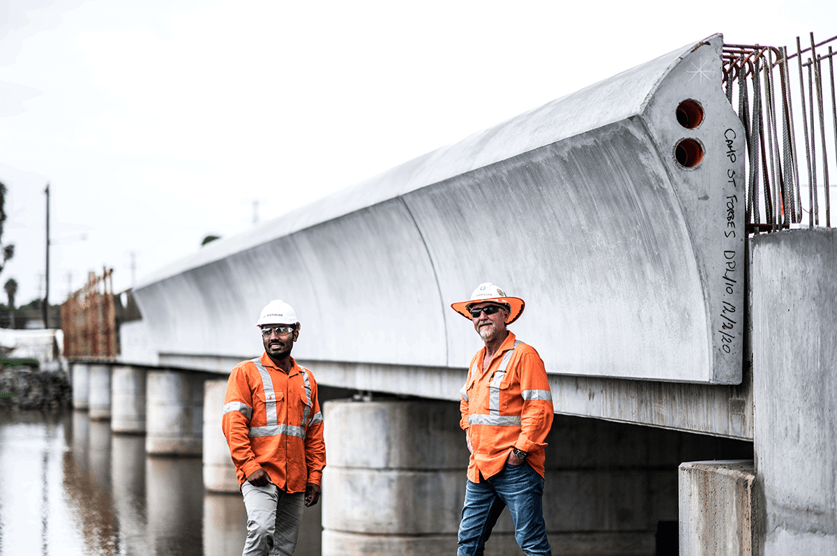 Two workers by Camp Street Bridge during Parapet Installation