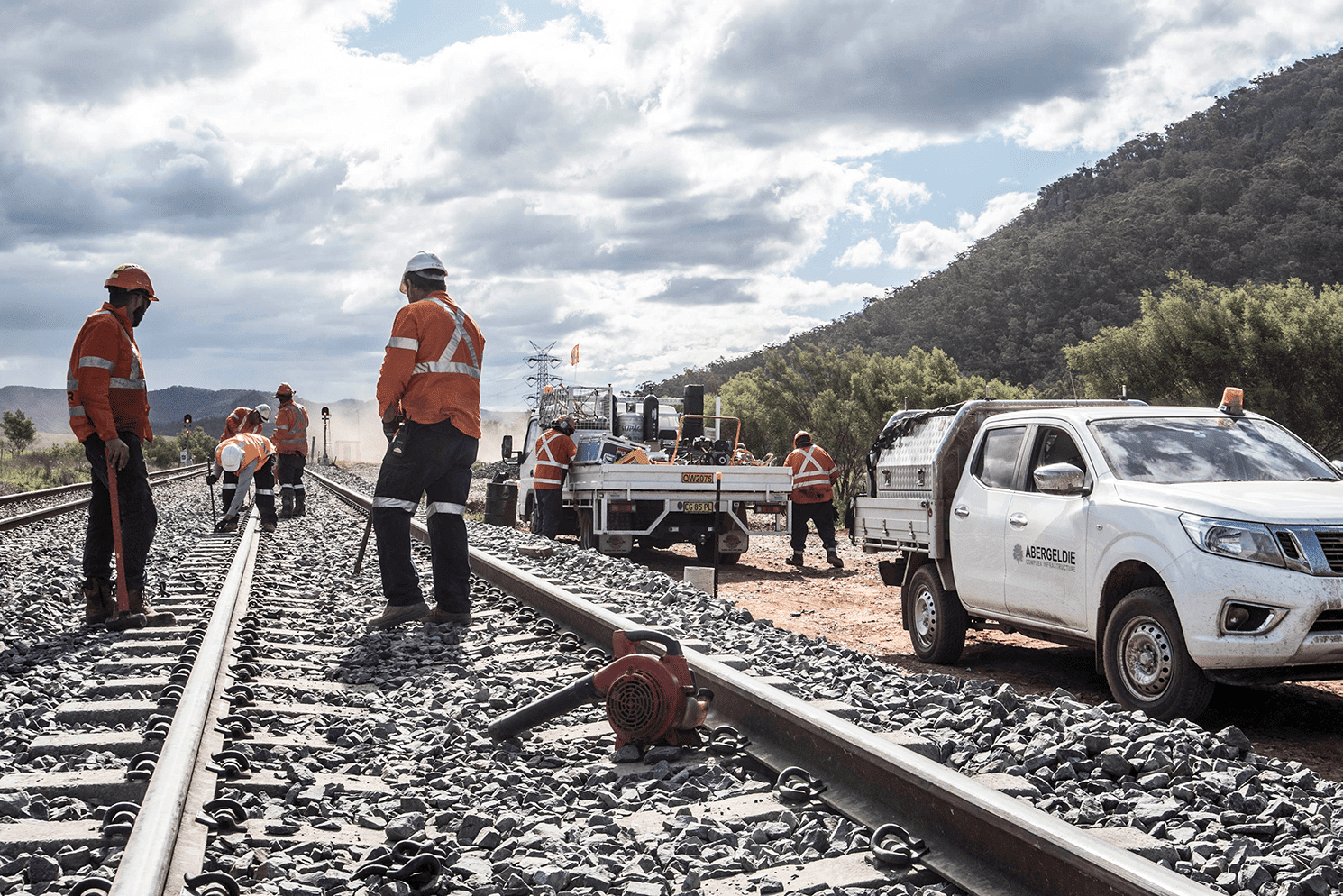 Workers standing on track looking onwards and an Abergeldie Car