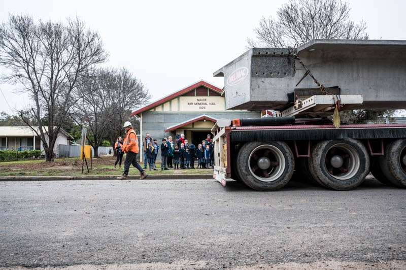 Ben Hagens safely transporting the girder in front of the Hay school children